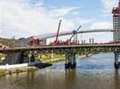 Dělníci začali vztyčovat první z oblouků nového Trojského mostu.