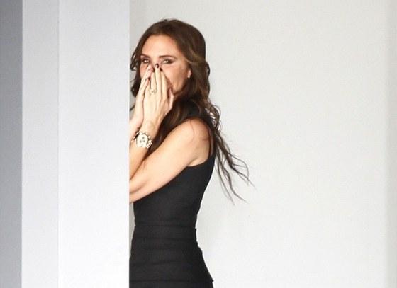 Úsměv, který nikdy nechtěla Beckhamová módnímu světu ukázat, zakryla rukama.