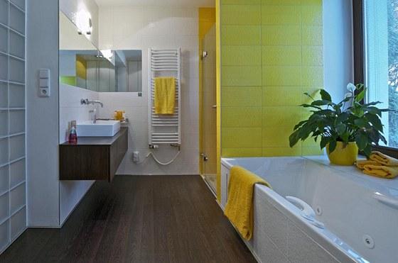 Koupelna p�sob� sv�tle a teple d�ky dv�ma okn�m um�st�n�m nad vanou a �lut�m