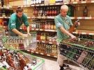 Zaměstnanci prodejny Globus na pražském Zličíne vyklízejí z regálu láhve