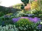 Květinová skalka v plném květu, vzadu vstup do užitkové části zahrady
