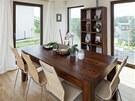 Jídelní stůl ladí s kuchyňskými dvířky, židle s dubovou podlahou.