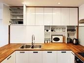 Kuchyň je také o kontrastu materiálů. Bílá barva ve vysokém lesku evokuje