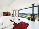 Obývací prostor navazuje na zahradu. Červený koberec je ozvěnou barevné