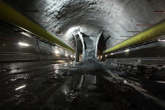 Ražení jednolodní stanice. Nejprve se Novou rakouskou tunelovou metodou zhotoví boční části. Poté tunelový bagr odtěží horninu v prostřední části mezi primárním ostěním. Nakonec se odtěží primární ostění.