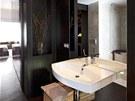 Koupelně vévodí velkoformátové zrcadlo za keramickým umyvadlem s baterií