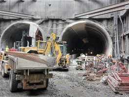 Portál ražené části stanice Veleslavín s již patrným definitivním trojlodním profilem. V popředí speciální vozidlo pro dopravu materiálů v tunelu.