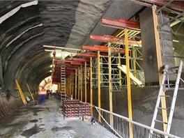 Pomocí tohoto trámu na pilířích se provádí složité navázání primárního ostění na primární ostění středního výrubu. Vybouráním ostění obou bočních tunelů vznikne propojený trojlodní tvar s celkovou šíří výrubu 22 m o ploše 175 m2 ve staniční části a 164 m2 v části technologické.