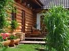 Na dřevěnou terasu volně navazuje svěží trávník, nároží domu ozvláštňuje...