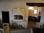 Krčma má otevřený oheň a připravené prostory pro kuchyň.