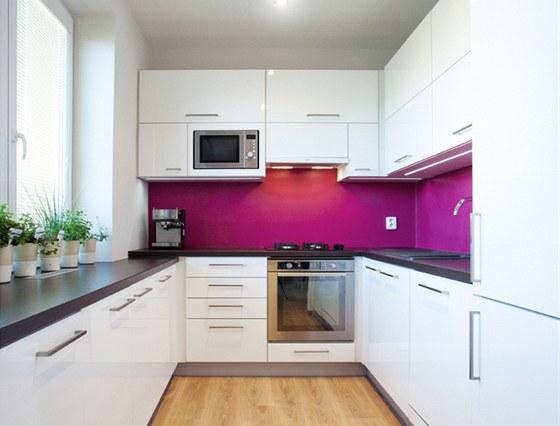 """Bílou kuchyni barevně """"rozsvítila"""" výrazná magenta."""