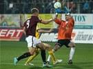 MÁM! Jaromír Blažek, gólman Jihlavy, chytá míč před dobíhajícím Bekimem Balajem ze Sparty.