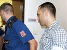 Justiční stráž přivádí obžalované Rolanda Ketu (vlevo) a Petra Skowrona. (29.