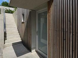 Z ulice vede k domu schodiště z betonových prefabrikátů sevřené betonovými