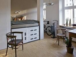 Vyvýšená postel je koncipována jako samostatný prostor s úložnou skříňkou a
