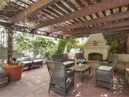 Na zahradě rezidence ve španělském koloniálním stylu je venkovní pergola s...