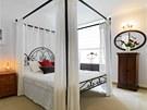 Ložnice pro hosty v provensálském stylu je vybavená kobercem v podobě přírodní