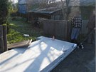 Jeden ze spadlých betonových panelů poničil i bránu do blízké zahrady.