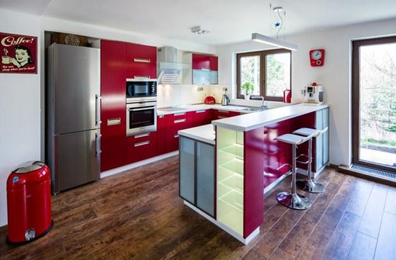 Výrazná dřevěná podlaha podtrhuje barevnost kuchyňské linky.