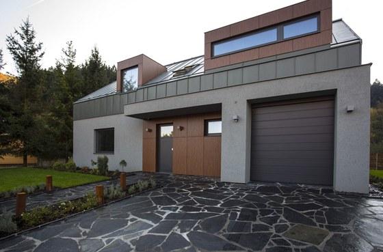Břidlicová dlažba pokrývá prostor před vstupem a garáží.