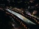 Noční pohled na budovu - cestu uprostřed naosvětlují žádné reflektory, světlo