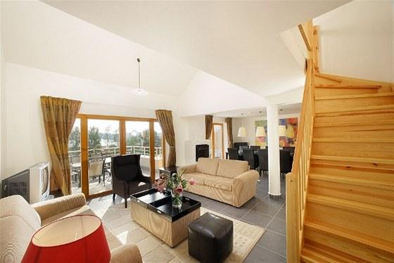 Prostorný obývák s krbem a velkou terasou nabízí nádherný výhled do krajiny.