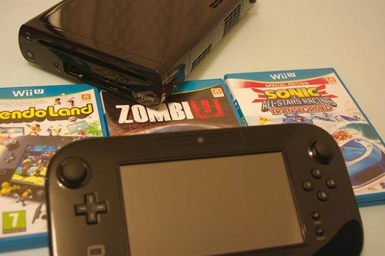 V pozadí konzole Wii U, v popředí tablet. Dominantou obalů od her je modrá barva. Na obrázku jsou tituly Nintendoland, ZombiU a Sonic All-Stars Racing.