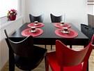 Nad stolem a židlemi Rauma (TON) září červené svítidlo (Ateh).