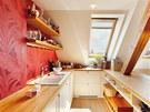 Červená barva září na tapetě za kuchyňskou deskou.