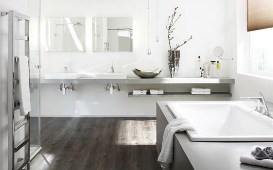 V koupelnách velmi úspěšně supluje dřevěné podlahy. Nevadí mu podlahové topení.