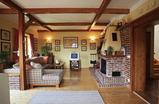V obývacím pokoji majitel nechal vyznít dřevěné sloupky a stropní trámy, mírně