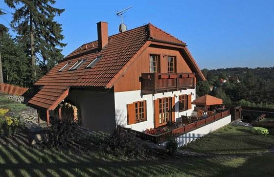Obývací pokoj je umístěn v západním průčelí domu a propojen francouzským oknem