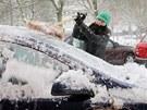 Dívka odmetá sníh ze svého auta v centru Plzně. (10. prosince  2012)