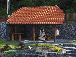 Vzadu za domem, v zákoutí u lesa, majitelé domu vybudovali letní kuchyni