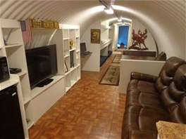Obývací prostor nabízí koženou pohovku a televizi, vedle je pracovní stolek s