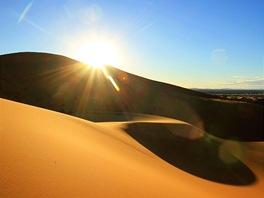 Slunce pomalu zapadá za jednu znejvětších písečných dun VMaroku.