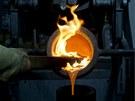 Odlévání zlata do formy. Dřevěným klackem slévač zabraňuje, aby se do formy...