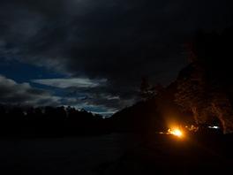 Sedíme na břehu řeky u plápolajícího ohně, nad námi září Jižní kříž. Na tohle