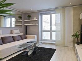 Mychalův byt. Základem obývacího pokoje je pohodlná sedačka ve světlé barvě....