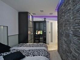 Michalův byt. Ložnice v pánském stylu je provedena v tmavých barvách. Zajímavým...