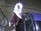 Žena zamyká nádrž vozu před tím, než ujede od pumpy bez placení.