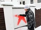 Ochotný soused odstraňuje rudou hvězdu z plotu okolo mlýna rodiny Černých a...