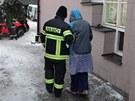 Hasič odvádí evakuovanou seniorku z DPS na Jičínské ulici v Příboře, kde při