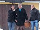 Miloš Zeman v doprovodu své ochranky kráčí z nákupu ke své chalupě.