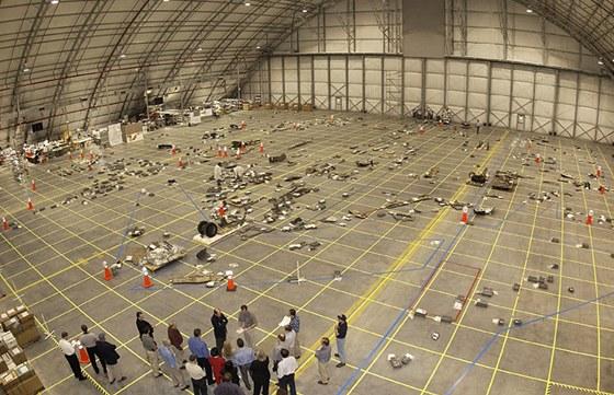 Ve velkém hangáru se specialisté pokoušeli z dochovaných trosek zjistit příčinu