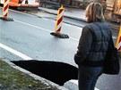 Propadlá vozovka přilákala i zvědavce. (31. ledna 2013)