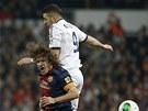 Karim Benzema (vpravo) z Realu Madrid v hlavičkovém souboji s Carlesem Puyolem