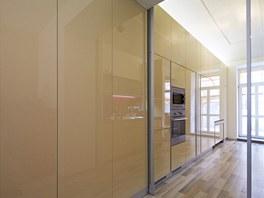 Lesklé plochy dávají prostoru hloubku. Posuvné skleněné dveře lze zcela