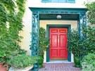 Vila s jasně červenými vchodovými dveřmi stojí na pozemku o rozloze 2,5...
