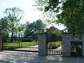 Na drátěný plot navazuje umělecky ztvárněná kovaná brána i branka, vsazené mezi...